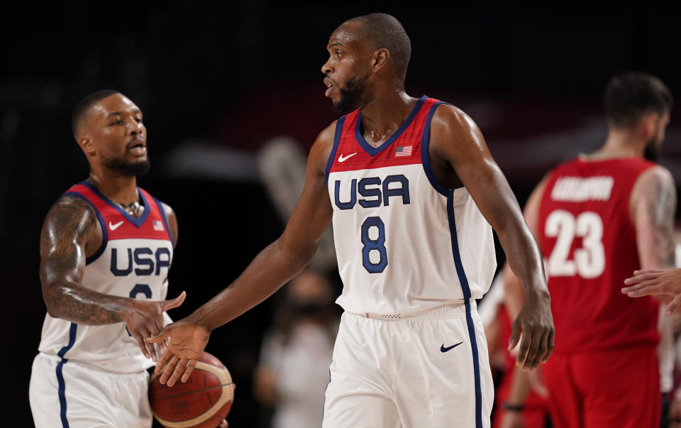 United States' Damian Lillard (6), left, and Khris Middleton (8) celebrate at the end of first quarter during men's basketball preliminary round game against Iran at the 2020 Summer Olympics, Wednesday, July 28, 2021, in Saitama, Japan. (AP Photo/Charlie Neibergall)