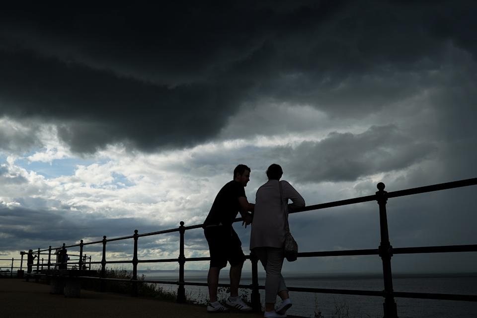 SALTBURN BY THE SEA, ENGLAND - AUGUST 02: A couple stand on the upper promenade as thunder clouds pass overhead on August 02, 2020 in Saltburn By The Sea, England. Heavy showers have continued through much of the day but will eventually give way to clearer skies into the evening. (Photo by Ian Forsyth/Getty Images)