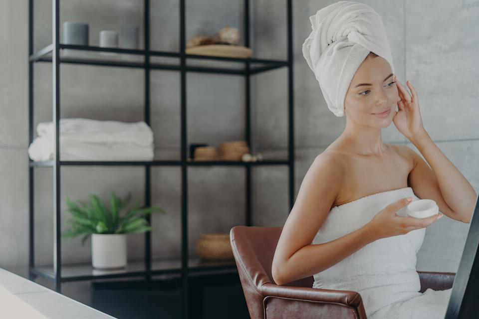 Attractive female model sits relaxed in armchair, applies cosmetic facial cream for healthy skin , looks into mirror, wrapped in bath towel, poses over bathroom interior, undergoes facial treatments.
