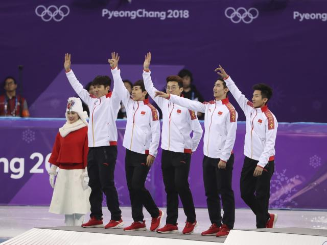 Short Track Speed Skating Events - Pyeongchang 2018 Winter Olympics - Men's 5000m Relay Final - Gangneung Ice Arena - Gangneung, South Korea - February 22, 2018 - Silver medallists, Team China wave on the podium. REUTERS/Lucy Nicholson