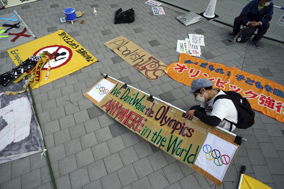 A participant against the Tokyo 2020 Olympics set to open in July, prepares banners to protest around Tokyo's National Stadium during an anti-Olympics demonstration Sunday, May 9, 2021 (AP Photo/Eugene Hoshiko)