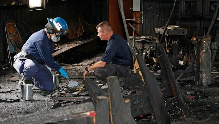 """<p>A state fire marshal, right, and an ATF agent collect evidence as they investigate the fire damaged Hopewell M.B. Baptist Church in Greenville, Miss., Wednesday, Nov. 2, 2016. """"Vote Trump"""" was spray-painted on an outside wall of the black member church. (AP Photo/Rogelio V. Solis) </p>"""