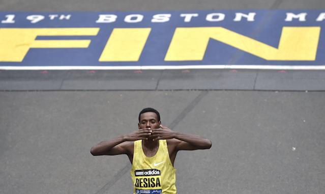 Lelisa Desisa, of Ethiopia, kisses his hands after crossing the finish line to win the men's division of the 119th Boston Marathon in Boston, Massachusetts April 20, 2015. REUTERS/Gretchen Ertl