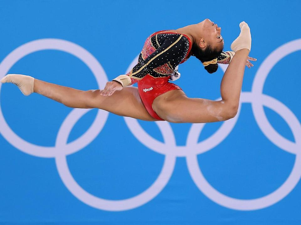 A gymnast bends in the air in front of the Olympic rings.