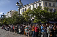 People wait outside the Athens Cathedral to pay respects to the late Greek composer Mikis Theodorakis in Athens on Monday Sept. 6, 2021. Hundreds of people have gathered outside Athens Cathedral where Greek composer and politician Mikis Theodorakis is to lie in state in a chapel of the cathedral for three days ahead of his burial on the southern island of Crete. (AP Photo/Petros Giannakouris)