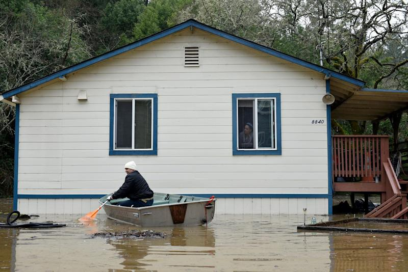 A man paddles a boat near a home surrounded by flood waters from the Russian River in Forestville, Calif., on Feb. 27, 2019. (Photo: Michael Short/AP)