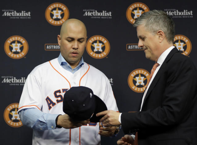 FILE - In this Dec. 5, 2016, file photo, Houston Astros general manager Jeff Luhnow, right, hands outfielder Carlos Beltran a cap during a news conference to announce Beltran's signing a one-year contract with the team, in Houston. Beltran is out as manager of the New York Mets. The team announced the move Thursday, Jan. 16, 2020. (AP Photo/David J. Phillip, File)