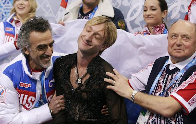 Evgeni Plushenko of Russia, centre, reacts in the results area after competing in the men's team free skate figure skating competition at the Iceberg Skating Palace during the 2014 Winter Olympics, Sunday, Feb. 9, 2014, in Sochi, Russia. (AP Photo/Darron Cummings, Pool)
