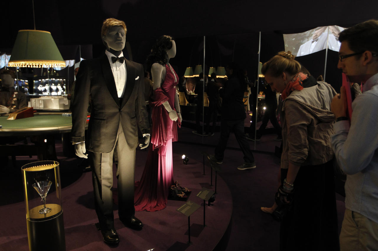 Visitors look at a tuxedo worn by James Bond actor, Daniel Craig, in the film 'Quantum of Solace' on display in the exhibition 'Designing 007 - Fifty Years of Bond Style' at the Barbican centre in London, Thursday, July 5, 2012. (AP Photo/Sang Tan)