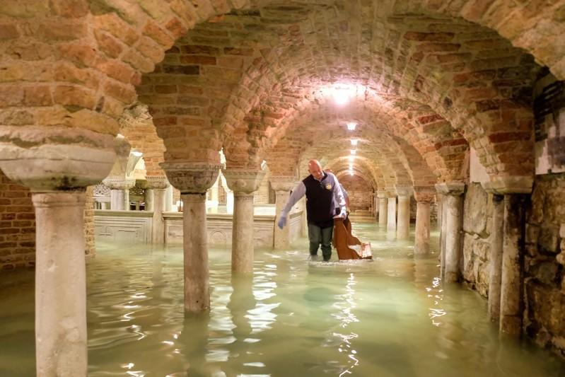 FILE PHOTO: A man wades in the flooded crypt of St Mark's Basilica during a period of exceptionally high water levels in Venice, Italy