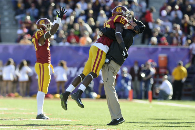 Southern California interim coach Clay Helton celebrates with wide receiver Nelson Agholor (15) after Agholor's 17-yard touchdown reception was ruled good against Fresno State in the second quarter of the Royal Purple Bowl NCAA college football game, Saturday, Dec. 21, 2013 in Las Vegas. (AP Photo/David Cleveland)