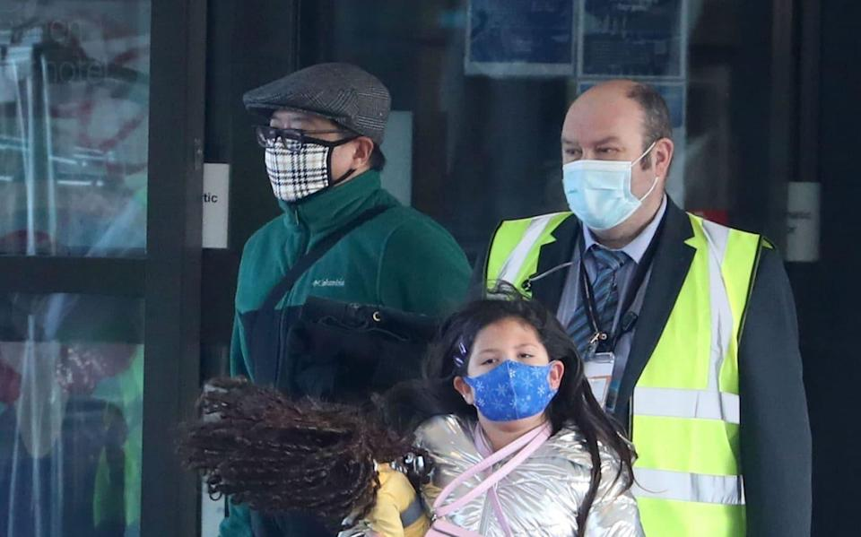 Chun Wong and his daughter Kiernan, eight, leave the DoubleTree by Hilton Hotel Edinburgh Airport after they where mistakenly made to quarantine in a hotel despite a loophole in the rules - PA