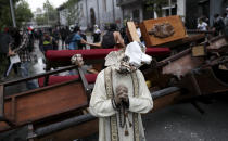 A damaged statue taken from a church forms part of barricade created by antigovernment protesters, in Santiago, Chile, Friday, Nov. 8, 2019. Chile's president on Thursday announced measures to increase security and toughen sanctions for vandalism following three weeks of protests that have left at least 20 dead. (AP Photo/Esteban Felix)
