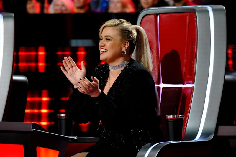 Kelly Clarkson sits on her The Voice chair mid-clap