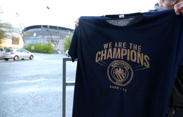A Manchester City fan holds up a 'We Are Champions t-shirt' at the Etihad Stadium