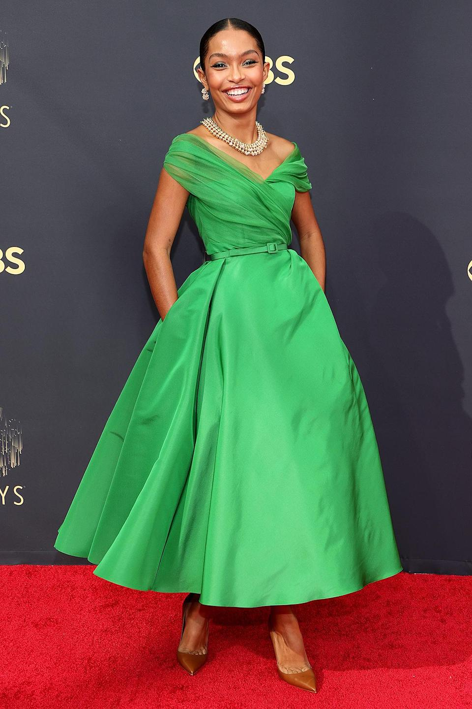 <p>looks ladylike in her off-the-shoulder Dior tea-length gown, accessorized with a thin matching belt, plus a collar necklace, statement earrings and pointy-toe Christian Louboutin pumps.</p>