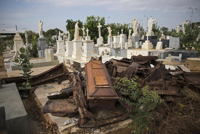 Looted coffins lay in a pile after grave robbers moved through El Cuadrado cemetery in Maracaibo, Venezuela, May 16, 2019. Daily burials used to happen until late afternoon, but the cemetery has tightened up on security, only holding burials until noon to deter grave robbers. (AP Photo/Rodrigo Abd)