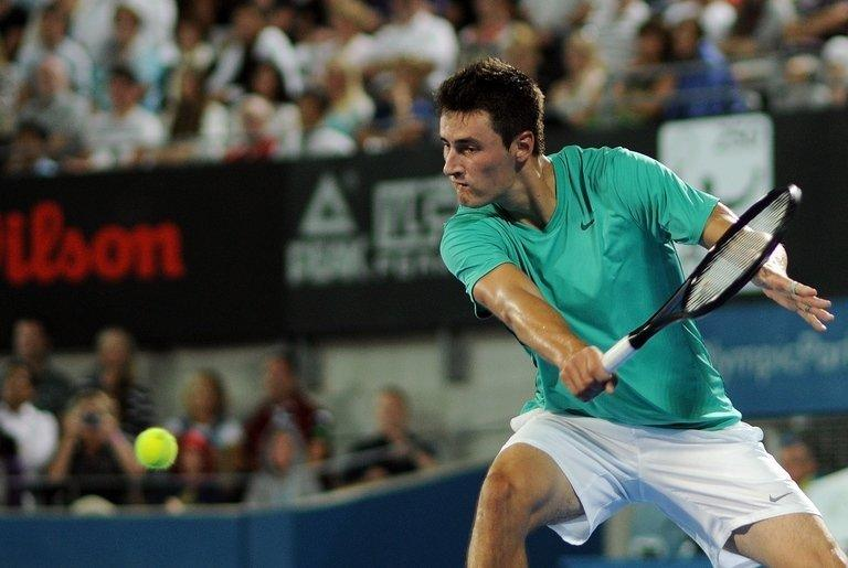 Bernard Tomic of Australia returns a shot against Jarkko Nieminen of Finland in Sydney on January 10, 2013