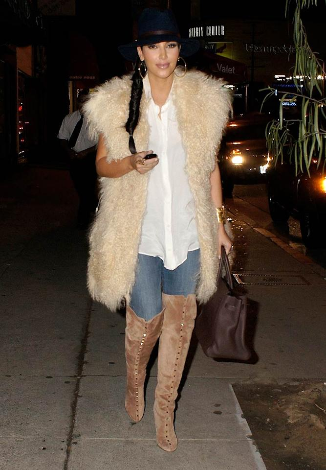 What's the worst part of Kim Kardashian's eyesore-inducing ensemble? Is it the reality TV titan's outdated fedora, her mangy faux fur vest, or her bejeweled, thigh-high boots? Surprisingly, we're leaning toward the boots. Discuss! (10/26/11)