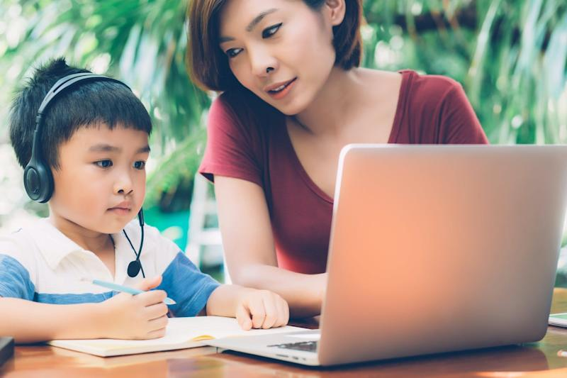 A young child sits outdoors in front of a laptop wearing headphones, while his mother, sitting next to him, leans towards him.