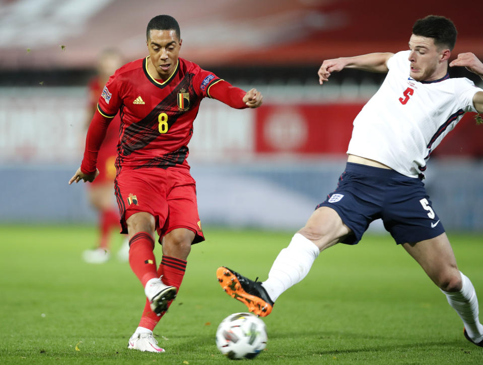 Belgium's Youri Tielemans, left, kicks the ball past England's Declan Rice to score his team's first goal during the UEFA Nations League soccer match between Belgium and England at the King Power stadium in Leuven, Belgium, Sunday, Nov. 15, 2020. (AP Photo/Francisco Seco)