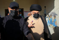 Populist Shiite cleric Muqtada al-Sadr, right, displays his ink-stained finger that shows he voted, at a polling center during the parliamentary elections in Najaf, Iraq, Sunday, Oct. 10, 2021. Iraq closed its airspace and land border crossings on Sunday as voters headed to the polls to elect a parliament that many hope will deliver much needed reforms after decades of conflict and mismanagement. (AP Photo/Anmar Khalil)