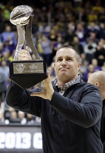 Northwestern football head coach Pat Fitzgerald holds the Gator Bowl Champion trophy as he celebrates with fans during the first half of an NCAA college basketball game against Michigan in Evanston, Ill., Thursday, Jan. 3, 2013. (AP Photo/Nam Y. Huh)