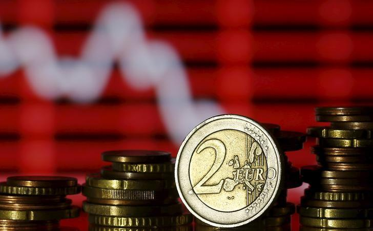 Euro coins are seen in front of a displayed stock graph in this photo illustration taken in Zenica