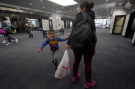 Yancarlos Amaya, 5, a migrant from Honduras, spins around his mother, Celestina Ramirez, during a layover at George Bush International Airport, Wednesday, March 24, 2021, in Houston. A few days ago, Yancarlos was walking along a muddy river bank after crossing the Rio Grande and landing on the U.S. side of the border with Mexico. Ramirez said they turned themselves in to U.S. Border Patrol officers and later spent hours in custody, a night under a bridge and three more days in a detention facility. (AP Photo/Julio Cortez)
