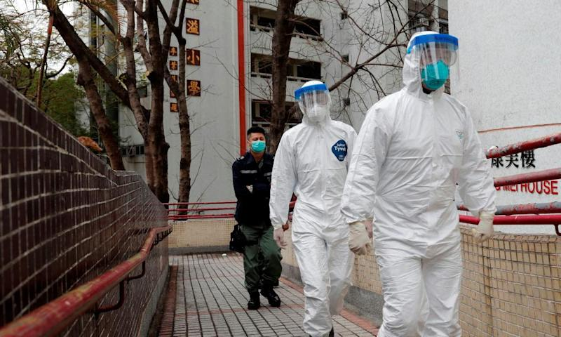 Health workers in protective gears evacuate residents from a public housing building in Hong Kong