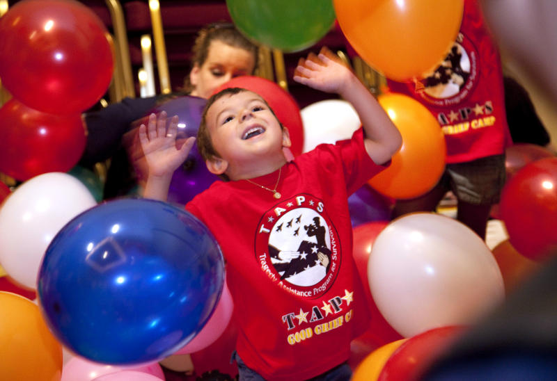 "In this photo taken Friday May 27, 2011, four year-old Raymond Sweet plays with balloons during ""Good Grief Camp"" in Arlington, Va., where nearly 500 children of fallen military members take part in activities with volunteer mentors on coping with grief and loss.  More than 4,300 children of U.S. troops killed in the Iraq and Afghanistan wars are growing up. Those interviewed at the camp, organized by the nonprofit Tragedy Assistance Program for Survivors every Memorial Day weekend, described it as one outlet that's allowed them to learn to work through their feeling. (AP Photo/Evan Vucci)"