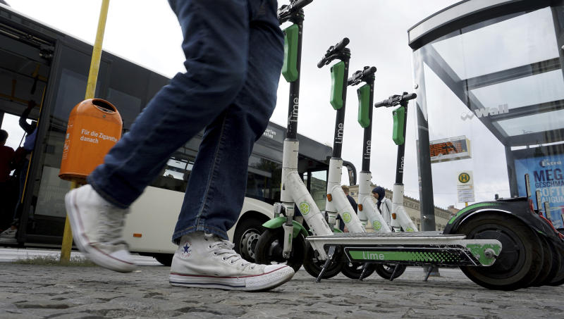In this Friday, Sept. 13, 2019 photo a traveller walks past electric scooter as he leaves a public bus in Berlin, Germany. (AP Photo/Michael Sohn)