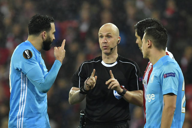 Marseille's Adil Rami, left, argues with British referee Anthony Taylor during their Europa League round of 16, 2nd leg, match between Athletic Bilbao and Olympique Marseille, at San Mames stadium, in Bilbao, northern Spain, Thursday, March 15, 2018. (AP Photo/Alvaro Barrientos)