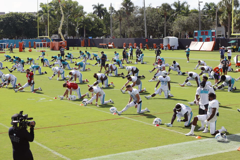 Miami Dolphins players stretch during NFL football training camp practice in Davie, Fla., Tuesday, Aug. 18, 2020. (AP Photo/Joel Auerbach)