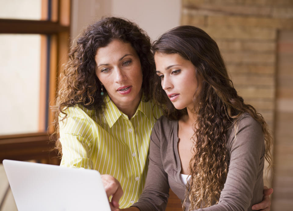 Mixed race mother and daughter using laptop together
