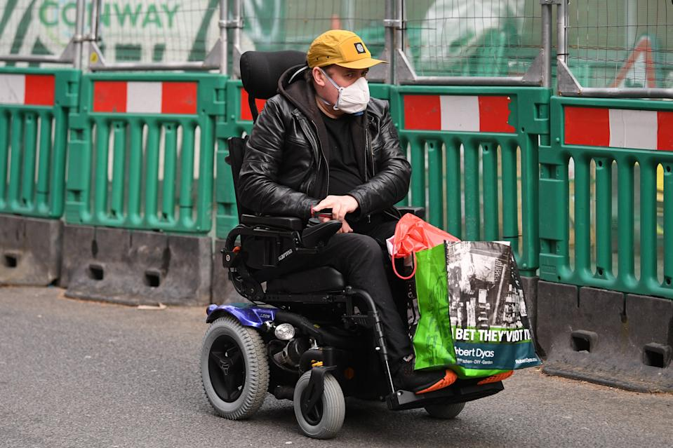 A pedestrian wears a protective facemask in Westminster, London, on the day that Health Secretary Matt Hancock said that the number of people diagnosed with coronavirus in the UK has risen to 51.