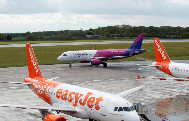FILE PHOTO: A Wizz Air Airbus A320 passes easyJet planes after landing at Luton Airport