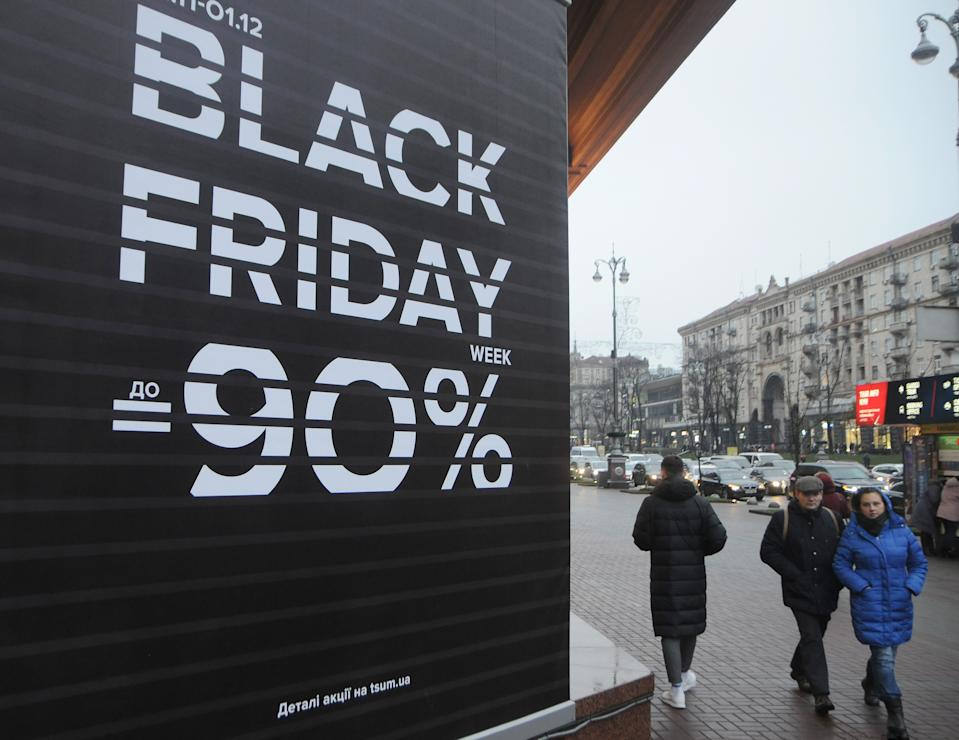 Shoppers walk past a Black Friday sales board. (Alexey Ivanov/SOPA Images/Sipa USA)