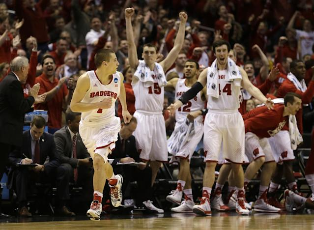 Wisconsin bench react after guard Ben Brust (1) made a three pointer against Oregon during the second half of a third-round game of the NCAA college basketball tournament Saturday, March 22, 2014, in Milwaukee. (AP Photo/Jeffrey Phelps)