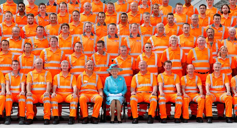 Queen Elizabeth II poses for a group photograph with Network Rail construction workers after opening the newly redeveloped Reading Railway Station on July 17, 2014 in Reading, England.