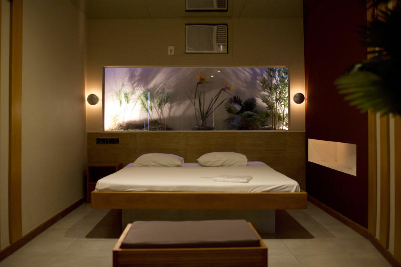 "A newly remodeled room is seen at the Shalimar Hotel, known as a love hotel in Rio de Janeiro, Brazil, Thursday, Jan. 17, 2013. Like about a third of city's 180 hotels that rent rooms by the hour, mostly for amorous rendezvous, the Shalimar is trading its oversized beds and bondage-ready chairs for proper couches, functional desks and other business-friendly furnishings. The goal is reinvention as a standard pay-by-the-day tourist hotel, after the government slashed property taxes for love hotels, known as ""motels"" in Portuguese, that agree to tone down the decor and free up 90 percent of their rooms for the tsunami of visitors expected to flood the city for the 2014 World Cup soccer tournament and the 2016 Olympic Games. (AP Photo/Felipe Dana)"