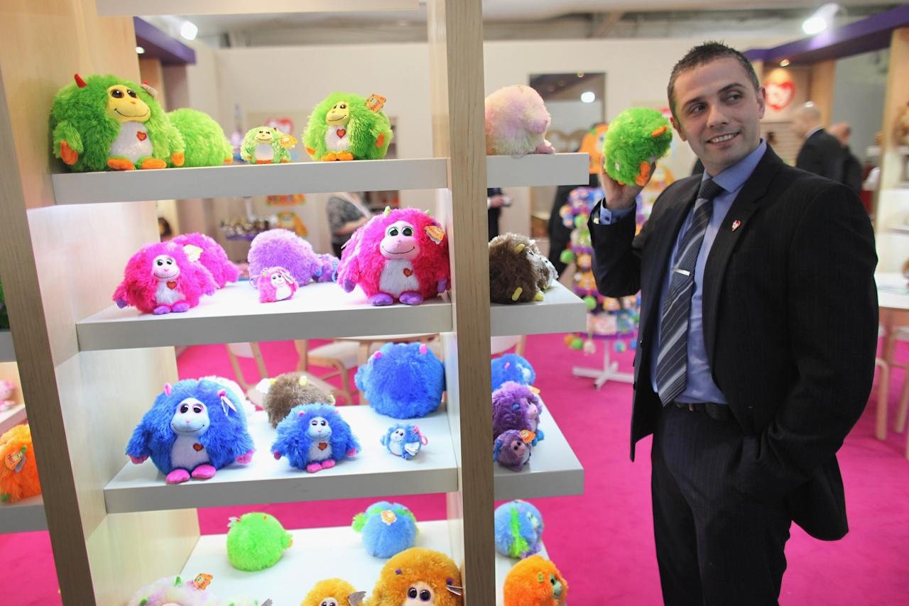 LONDON, ENGLAND - JANUARY 24:  A sales representative listens to the noises made by a 'Monstaz' toy on display at  the 2012 London Toy Fair at Olympia Exhibition Centre on January 24, 2012 in London, England. The annual fair which is organised by the British Toy and Hobby Association, brings together toy manufacturers with retailers from around the world.  (Photo by Oli Scarff/Getty Images)
