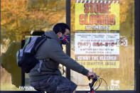 FILE - In this Friday, Nov. 6, 2020, file photo, a man wearing a face mask rides a bicycle past a closed store in Wilmette, Ill. States in the U.S. are renewing their push for more federal money to deal with the fallout from the coronavirus outbreak and to help them distribute a vaccine when one becomes widely available sometime in 2021. (AP Photo/Nam Y. Huh, File)
