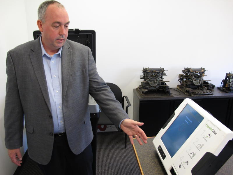 In this Friday, Aug. 16, 2019 photo, Mac Beeson, Regional Sales Manager at Election Systems and Software, demonstrates one of his company's digital voting machines in Raleigh, N.C. The state elections board declined Thursday, Aug. 22, 2019 to decide whether the next generation of voting machines should be required to furnish a paper printout so voters can read and confirm their ballots. (AP Photo/Allen G. Breed)