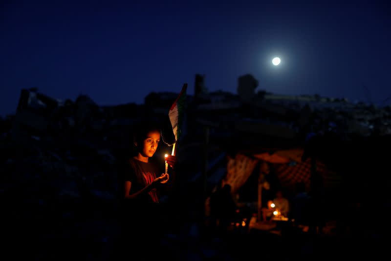 A Palestinian from Zawaraa family holds a candle near a makeshift tent amid the rubble of their houses which were destroyed by Israeli air strikes during the Israeli-Palestinian fighting in Gaza