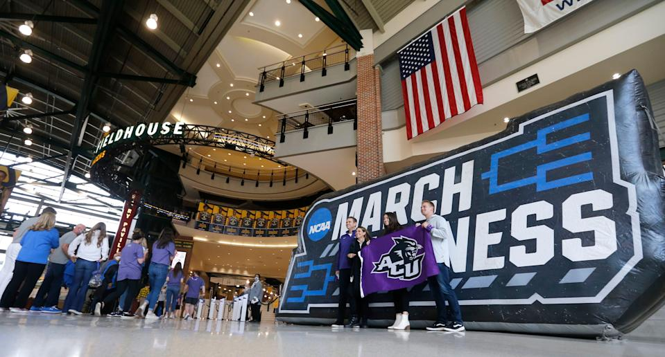 Fans take pictures near signage before the UCLA-Abilene Christian men's NCAA Tournament game at Bankers Life Fieldhouse in Indianapolis.