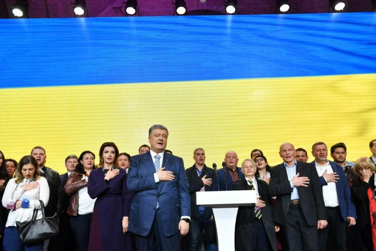 Outgoing Ukrainian President Petro Poroshenko (C) conceded defeat shortly after polls closed