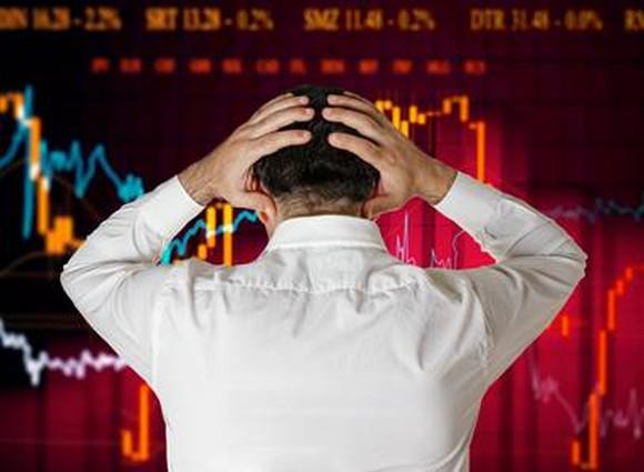 A man holds his head in his hands while staring at a chart of a declining share price.