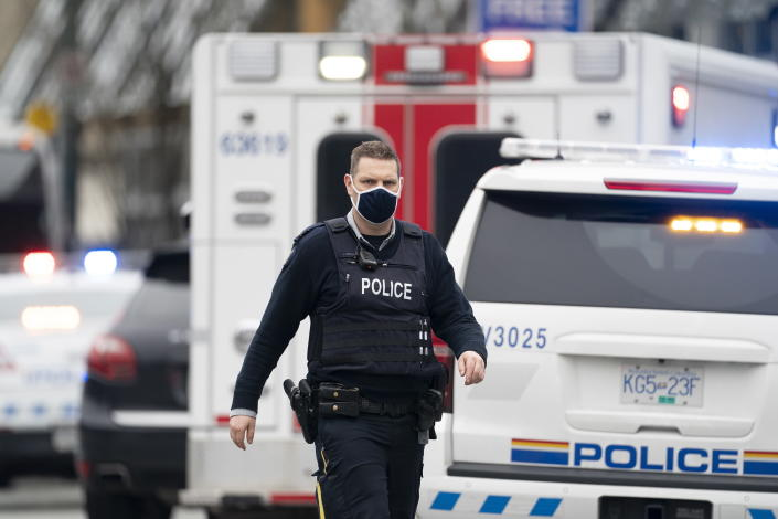 Members of the RCMP are seen outside of the Lynn Valley Library, in North Vancouver, British Columbia, Saturday, March 27, 2021. Police say multiple victims were stabbed inside and outside the library today. (Jonathan Hayward/The Canadian Press via AP)