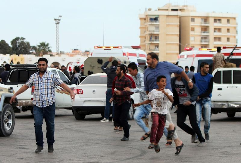 Libyan demonstrators run for cover from shelling during a protest in Benghazi calling for military forces to re-capture the southern city of Sirte from the Islamic State group without foreign intervention on May 6, 2016